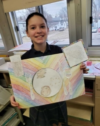 Sixth grade student showing her descriptive writing project