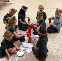 Kindergarten students stacking cups during a STREAM activity for the 100th day of school.